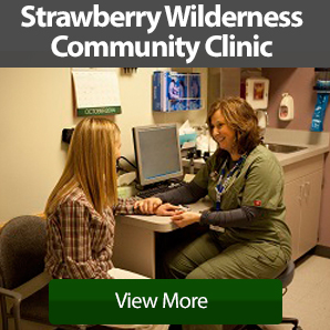 Strawberry Wilderness Community Clinic exam room with a young female patient having her pulse taken by a female medical assistant in scrubs