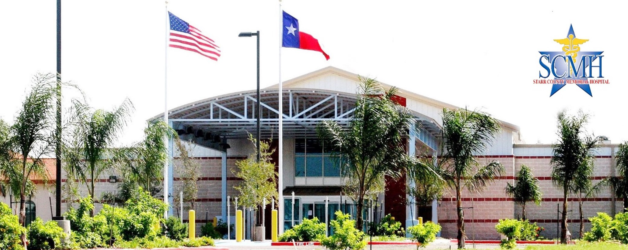 The front exterior of Starr County Memorial hospital on a sunny day with an American and a Texas flag blowing in the wind