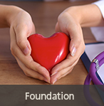 "A red object shaped like a heart that is being cupped by both hands of a Caucasian woman- links to ""Foundation"" page"