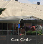 Photo of the front of the Blue Mountain Care Center with surrounding bushes and hanging flowers