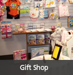 "Picture of gift shop with items for sale, including stuffed animal, baby clothing and blankets- links to ""Blue Mountain Hospital Auxiliary"" page"