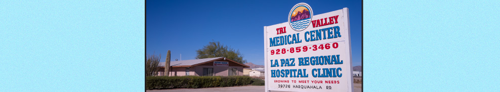 """An image of the medical center on a blue and cloudless day with a sign that says, """"Ti Valley Medical Center, 928-859-3460. La Paz Regional Hospital Clinic, growing to meet your needs."""