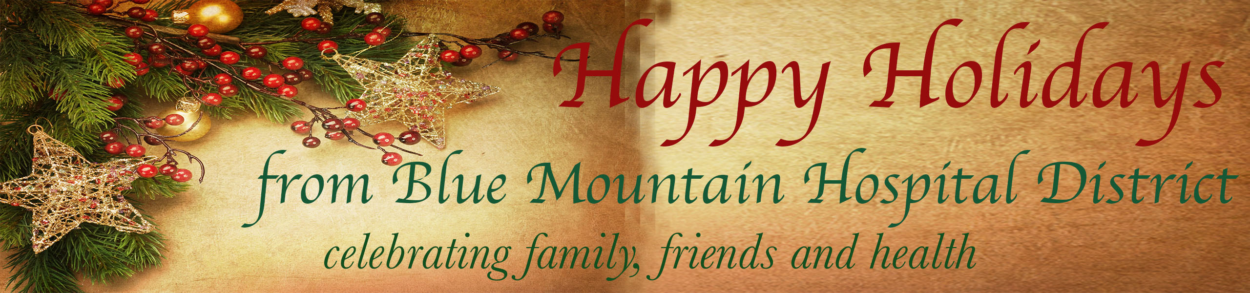 """""""Happy Holidays from Blue Mountain Hospital District celebrating family, friends & health""""- 2 gold snowflake ornaments, two round gold ornament balls, red holly berries and evergreen branches to the left of a tan background"""