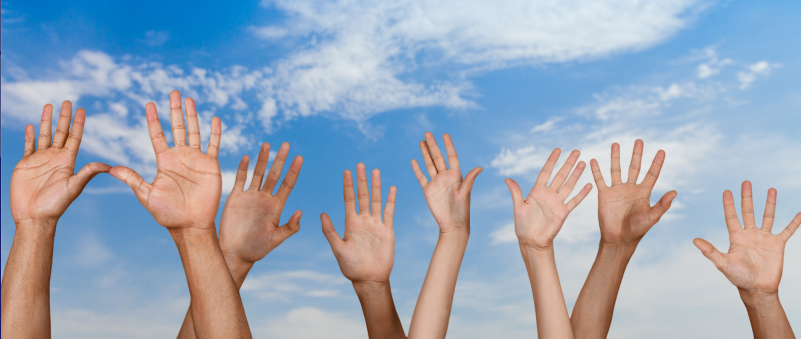 Photo of four pairs of hands in the air and a blue sky with clouds in the background