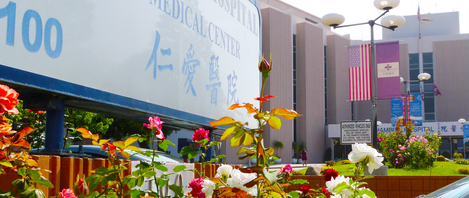 Alhambra Hospital Medical Center exterior: flowers are blooming in front of the hospital sign