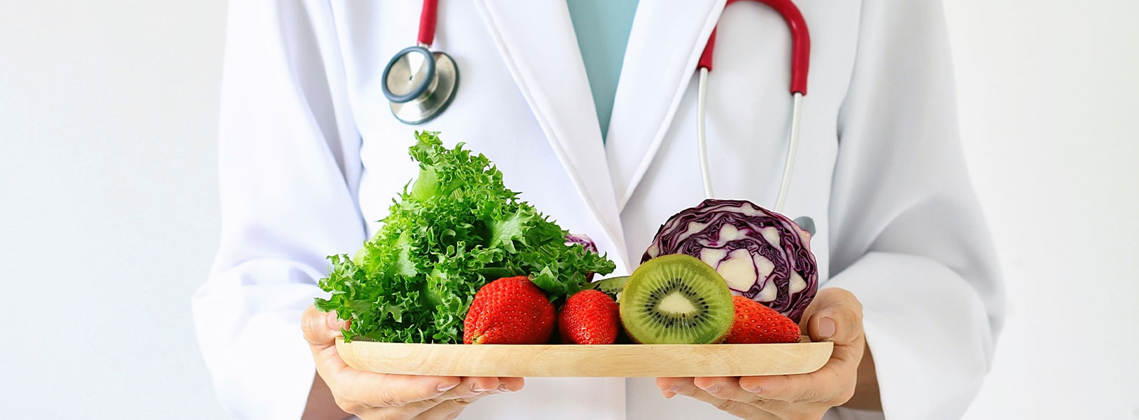 A nutritionist is holding a plate of fruit and vegetables