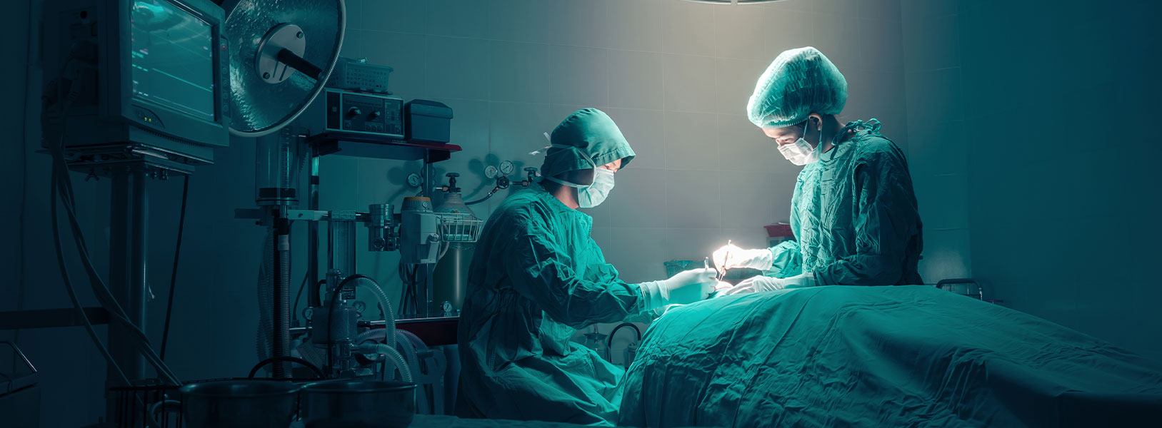 Two surgeons in full operating gear are operating on a patient