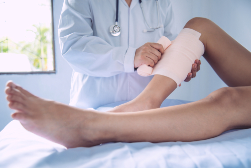 A physician is bandaging an injured leg