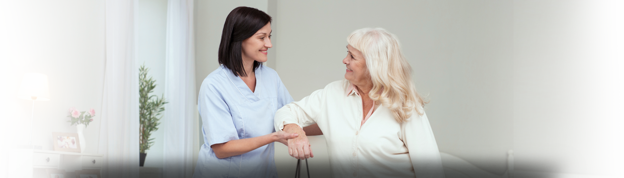 A smiling nurse wearing blue scrubs is assisting an elderly woman with arm exercises.