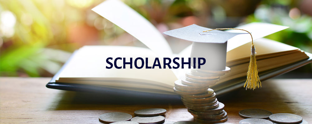 Scholarship: a stack of coins with a paper diploma hat placed on top and a book in the background