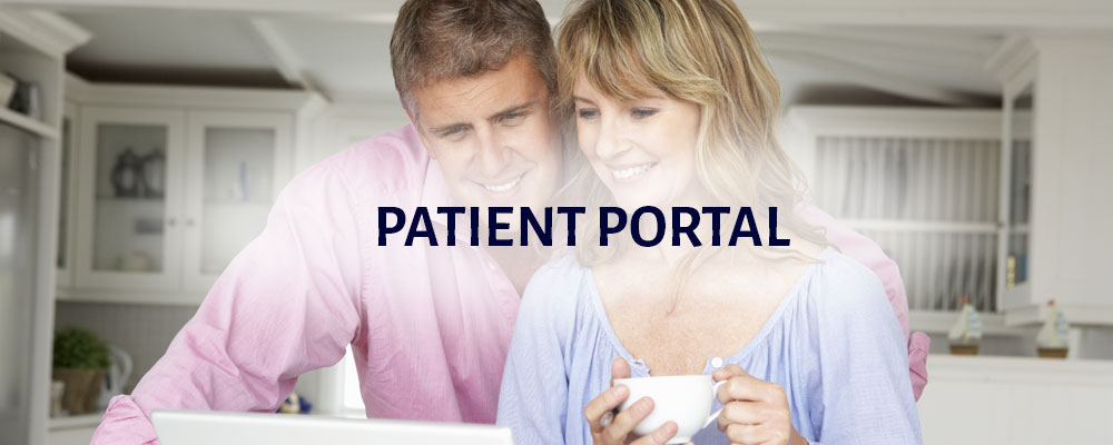 Patient Portal: a younger couple are smiling and looking at a computer screen