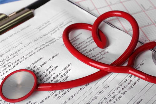 A red stethoscope is twisted into a heart and placed onto a clipboard