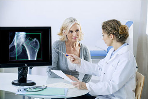 An image of an x-ray on a computer screen and a female patient listening to the doctor speak
