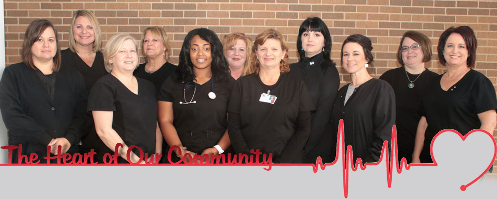 A group photo of eleven smiling nurses wearing black scrubs