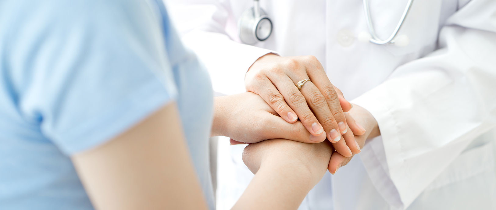 A doctors hand is placed over a patient's hand in comfort