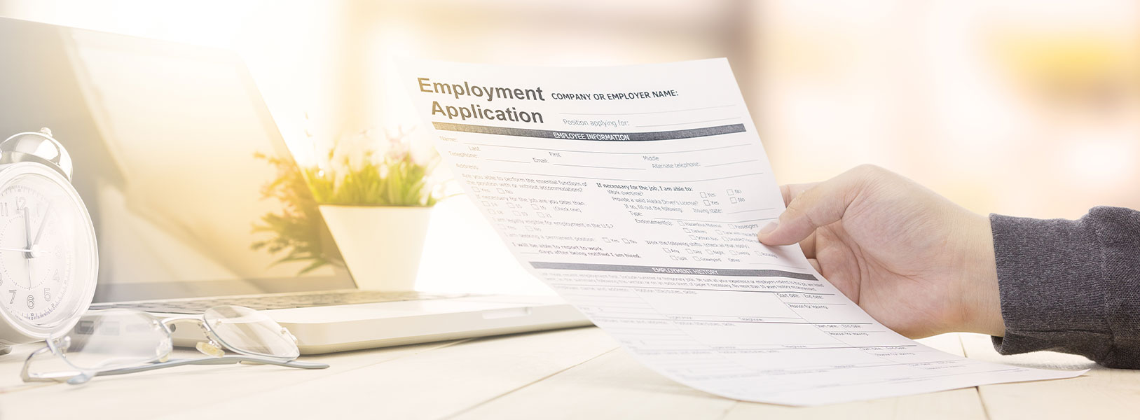 An image of a hand holding an employment application