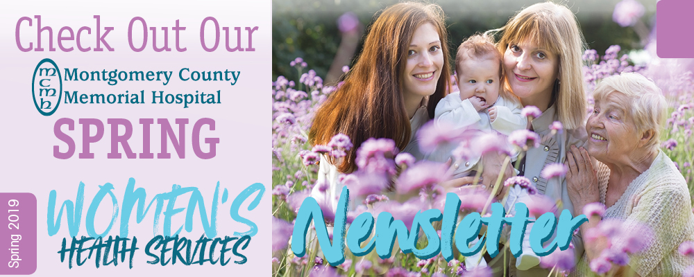 A grandmother, mother, daughter,and granddaughter are sitting in a field of flowers.