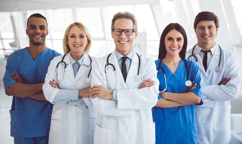A row of smiling doctors and nurses crossing their arms