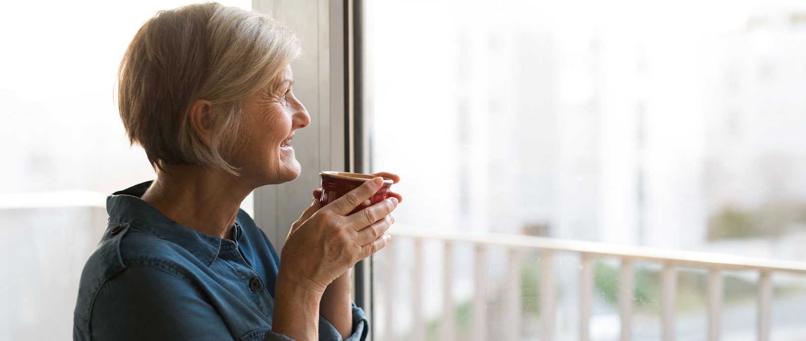 Photo of an elderly woman staring out the window smiling and drinking out of a coffee mug