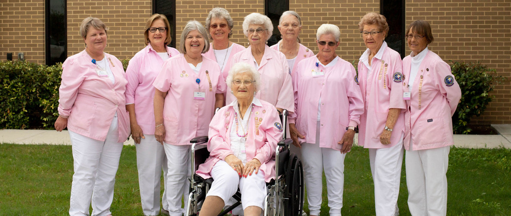 a picture of 10 older ladies all wearing pink nurses jackets with white scrub pants
