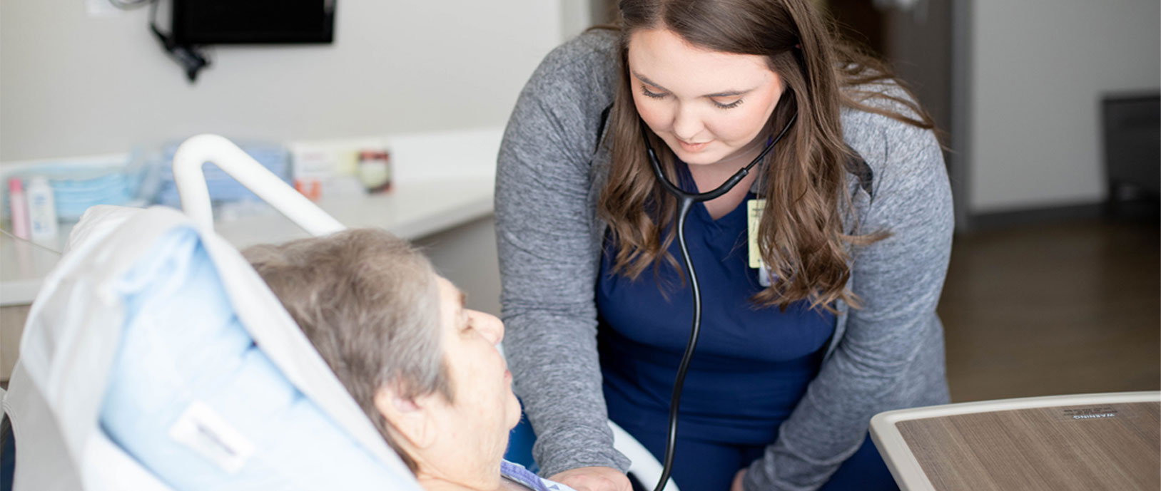a nurse checking breath sounds on a patient laying in a hospital bed.