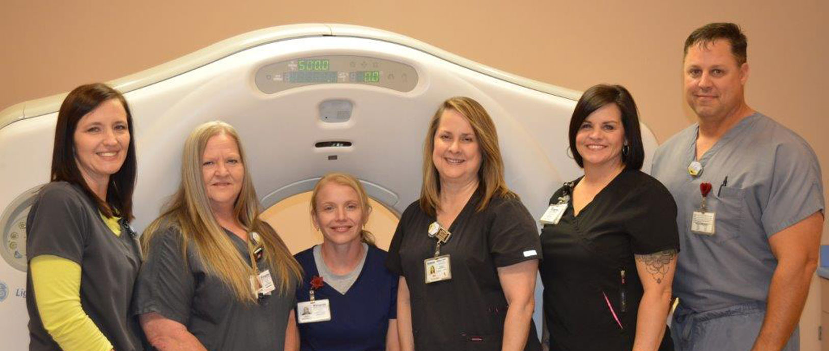 The Radiology staff in front of a ct machine