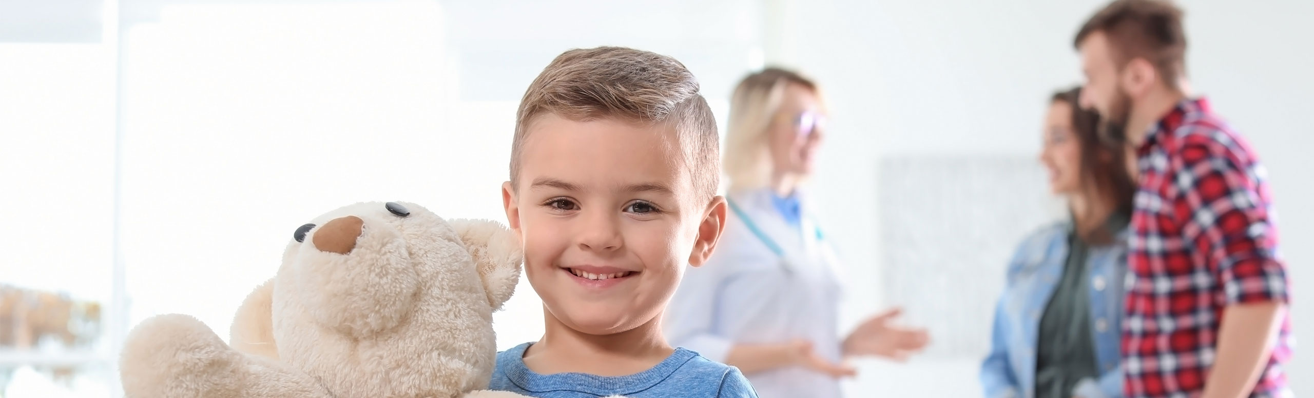 A child holding a teddy bear, with doctor talking to a parent in the background.