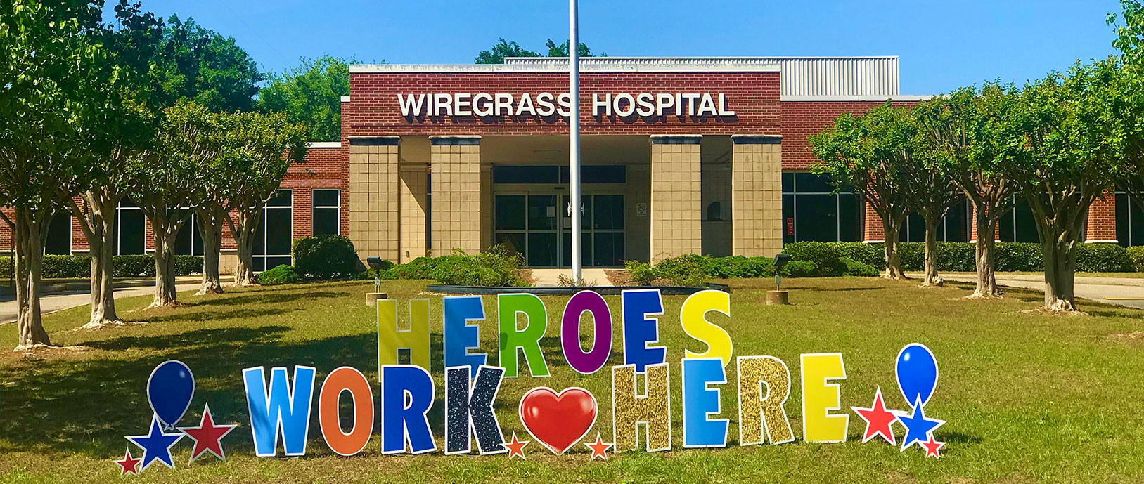 Pictured is a photograph of our hospital with a sign in from saying Heroes Work Here.