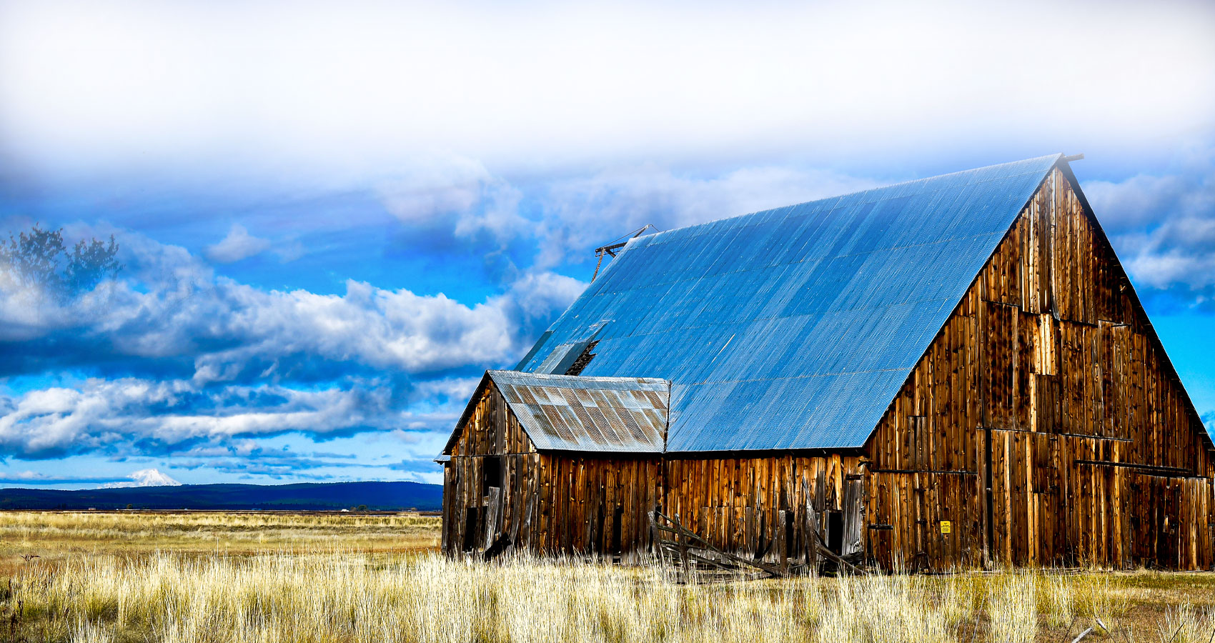 This is a picture of a barn in field with mountains in the background.