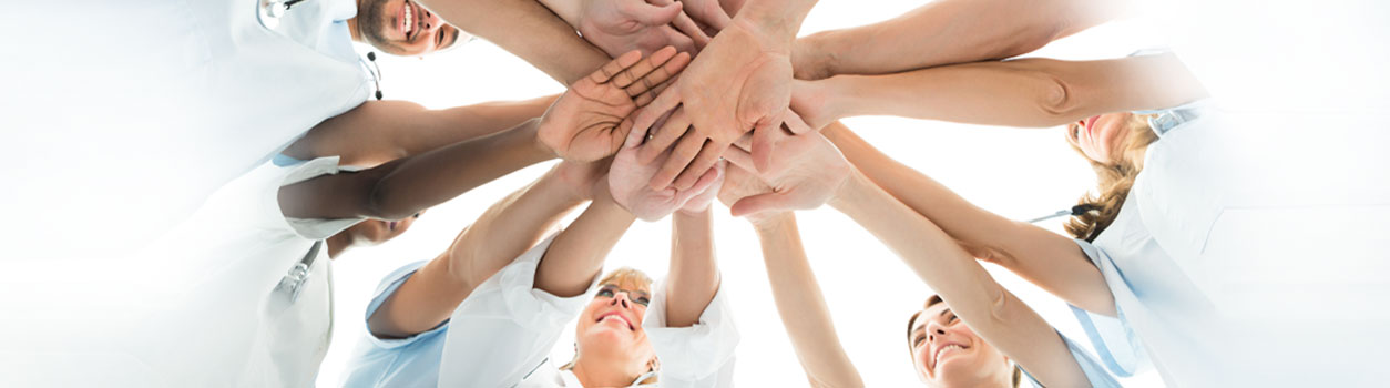 This is a picture with doctors and nurses hands in together in a circle.