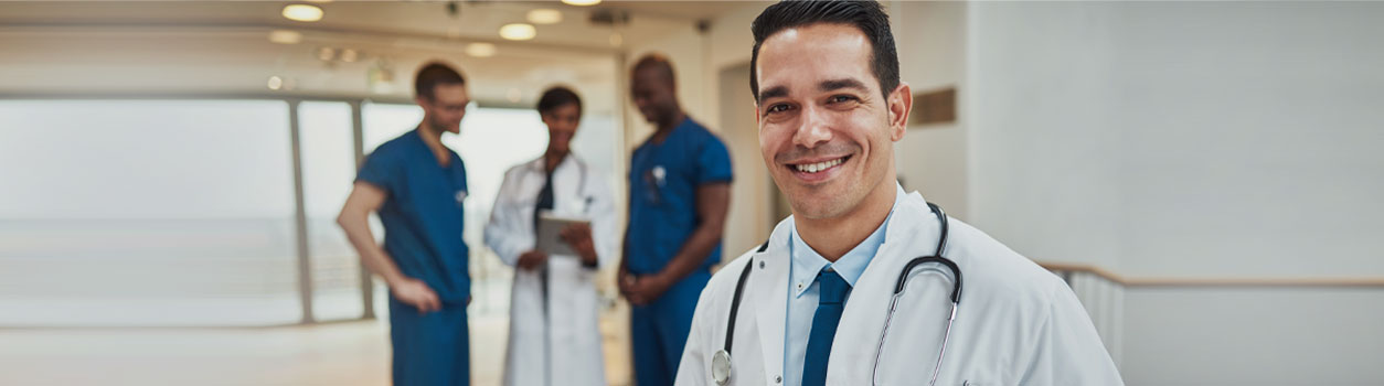 This is a picture of a doctor smiling with another doctor and two nurses in the background looking at a file.
