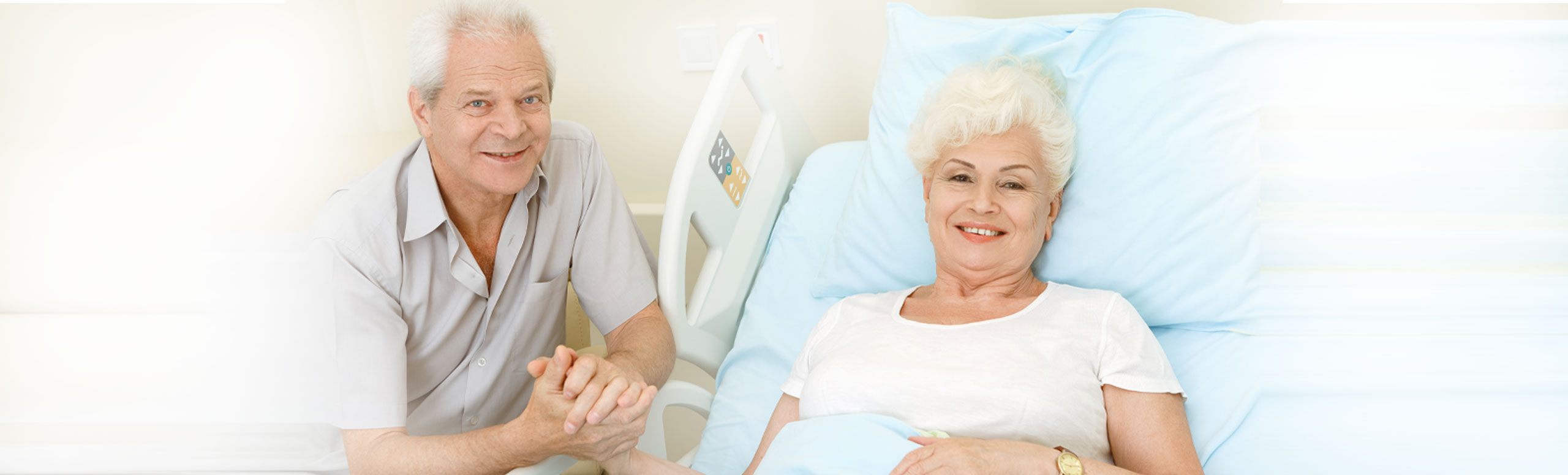 This is a picture of a elderly couple. One is laying in a hospital bed.