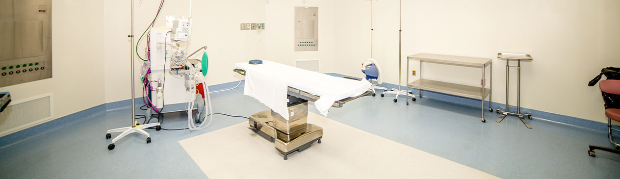 Banner picture of a Surgical Room. There is a table bed with medical equipment.