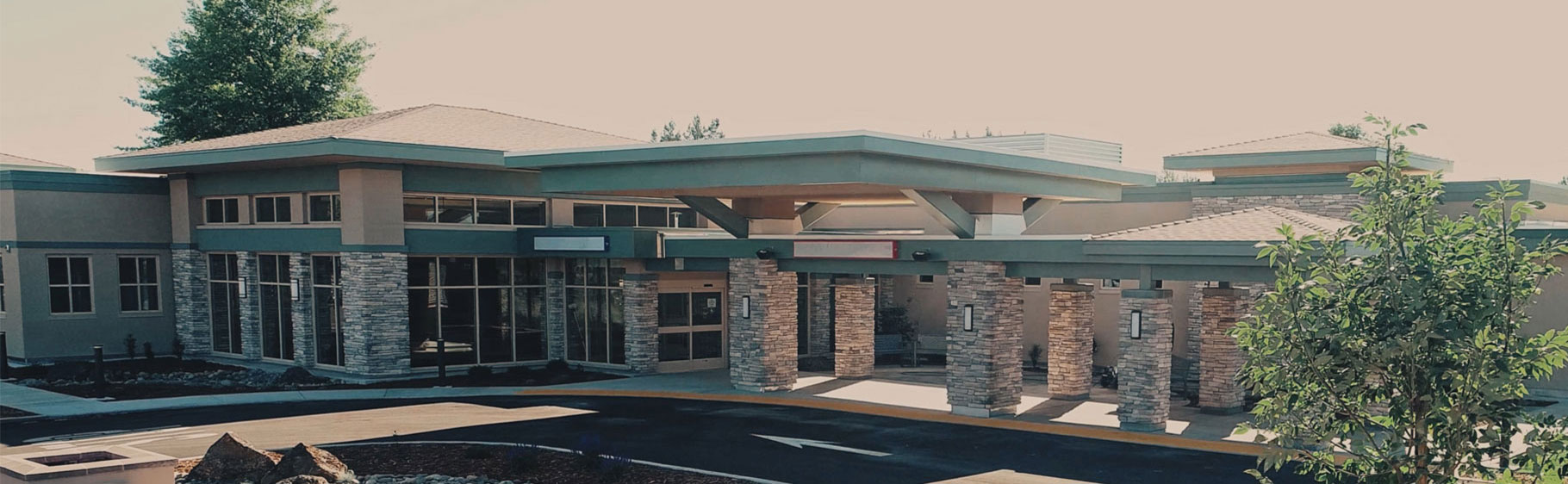 Banner picture of Mayers Memorial Healthcare Hospital. There is two trees and some rocks outside of the building