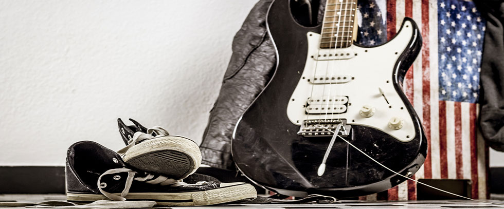 A pair of shoes in front of a guitar