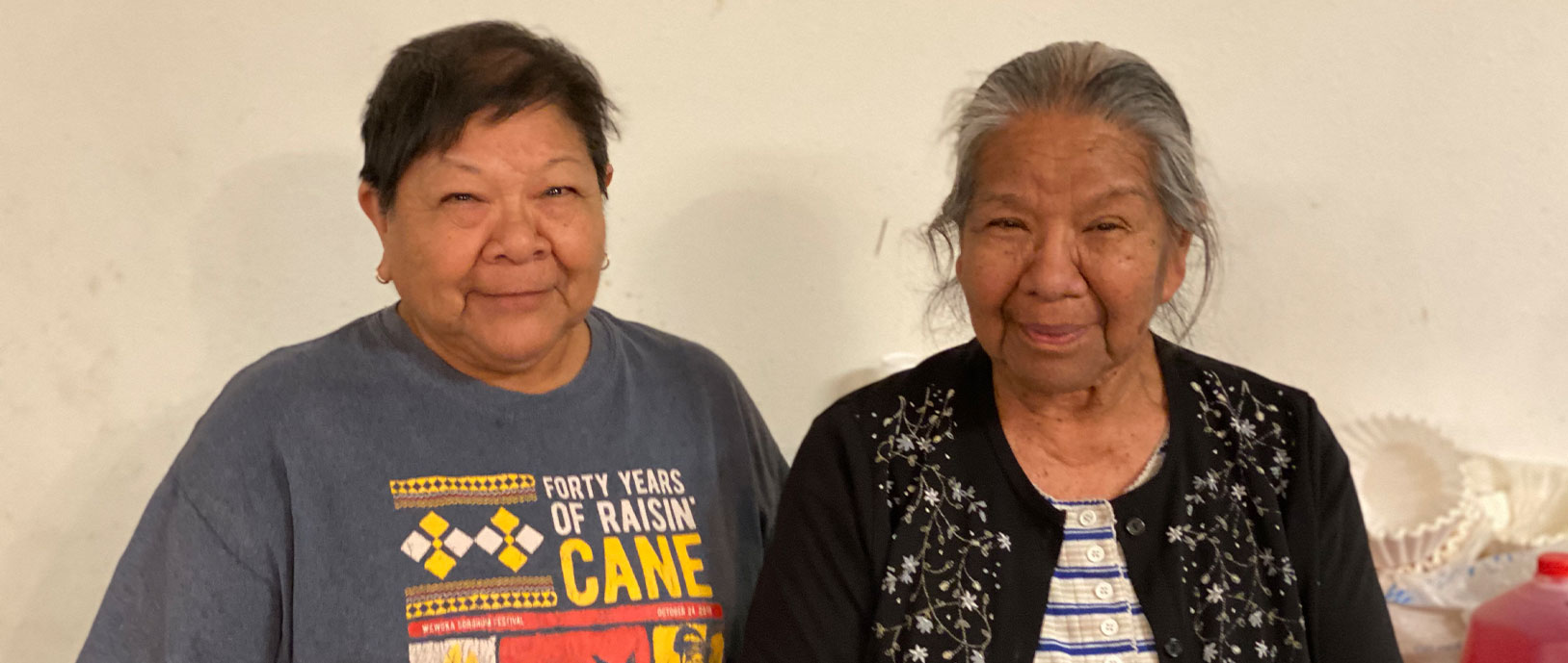 A photo of two female tribal members smiling for the camera