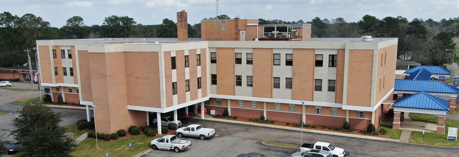 A view of the Mizell Memorial Hospital with cars parked in the parking lot