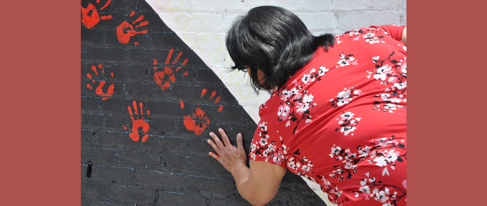 Picture of a female putting her hand print on a brick wall that has other handprints on it as well.