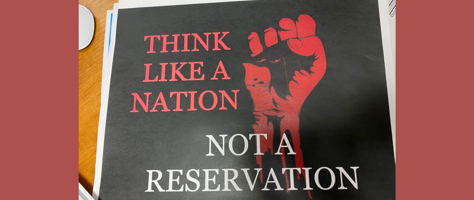 Paper with a fist up. It says:  THINK LIKE A NATION NOT A RESERVATION