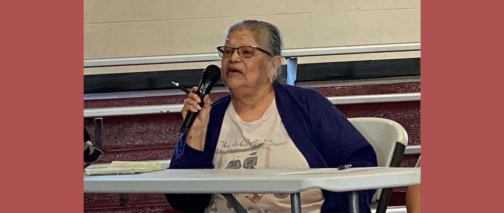 Picture of an elderly lady sitting at a table holding a microphone up to her mouth